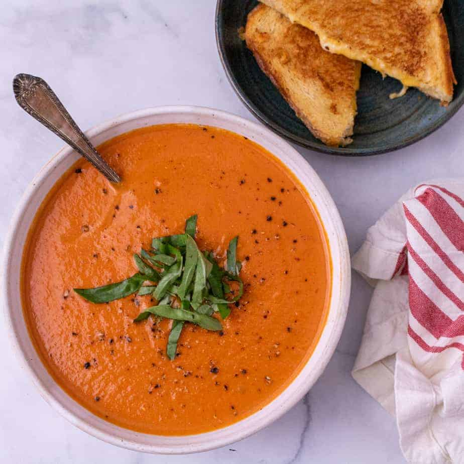 A white bowl of tomato bisque garnished with basil with a spoon. A green plate of grilled cheese is partially visible in the top right corner. A folded red and white napkin is partially visible in the bottom right corner.