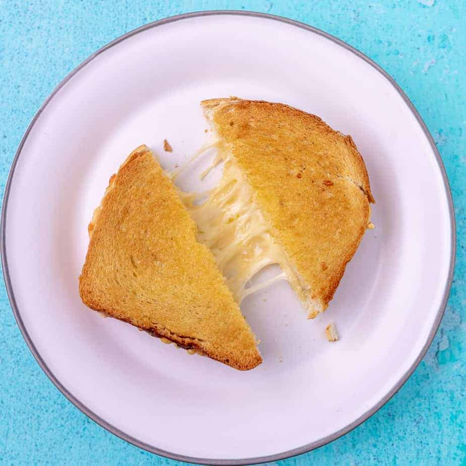 A diagonally cut grilled cheese, pulled slightly apart to show cheese pull on a white plate.