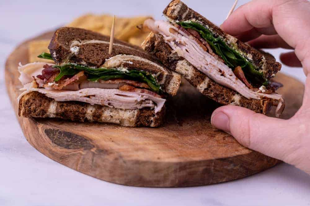 Two halves of a turkey sandwich next to each other on a wooden plate with a hand grabbing the right half of the sandwich.