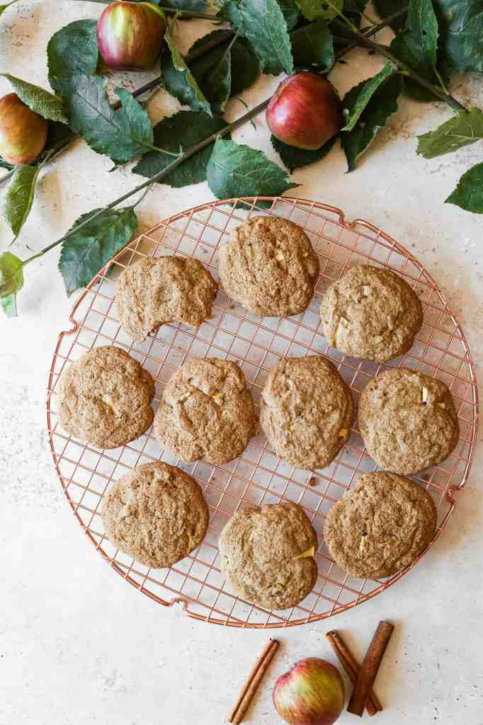 a cooling rack of gluten free apple spice cookies with apple branches and apples surrounding it