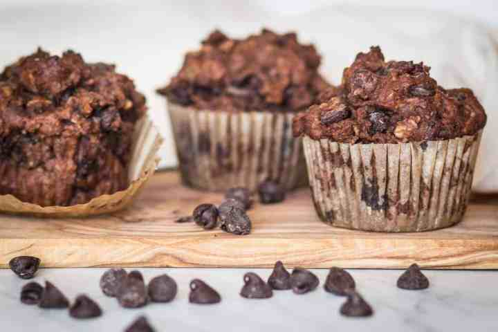 three gluten free chocolate zucchini muffins on a cutting board with chocolate ships sprinkled around
