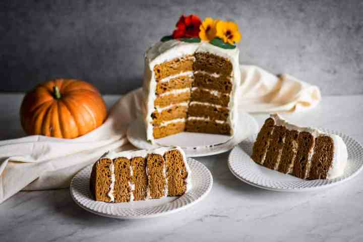 two slices of gluten free pumpkin cake with cream cheese in front of the five layer cake