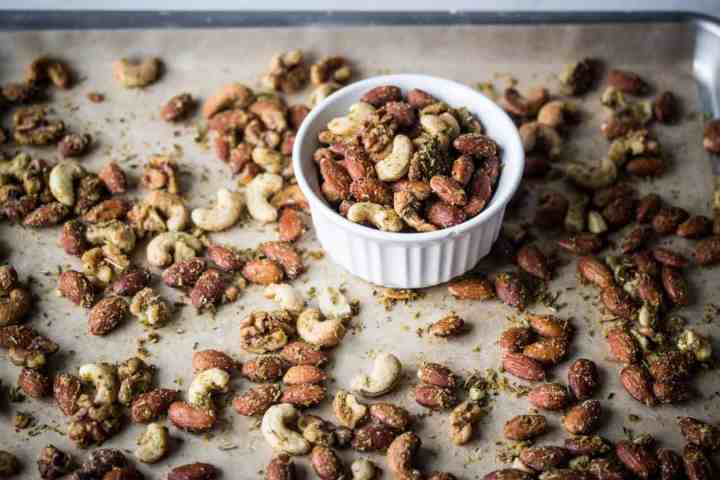 gluten free air fryer savory herb roasted nuts in a dish on a baking sheet