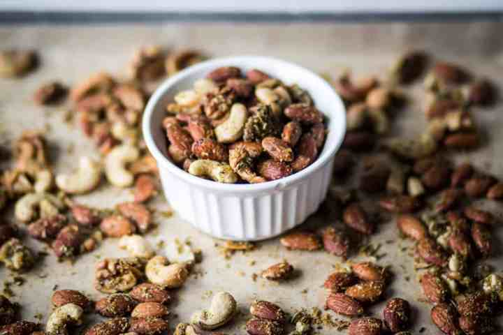 gluten free, low carb, paleo and whole30 air fryer savory herb roasted nuts in a white dish
