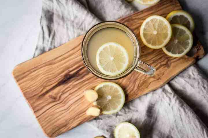 a mug of healthy lemon ginger tea with a lemon slice in it