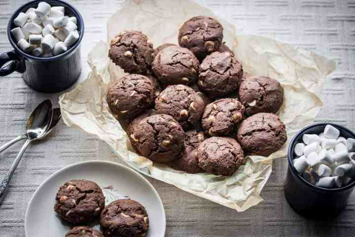 a basket of gluten free hot cocoa cookies with mugs of hot chocolate