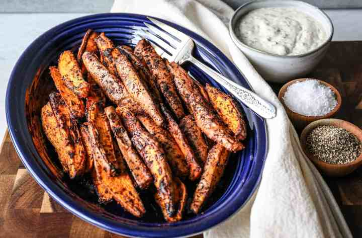 a blue fiesta ware platter of air fryer sweet potato wedges with a bowl of gluten free ranch dressing