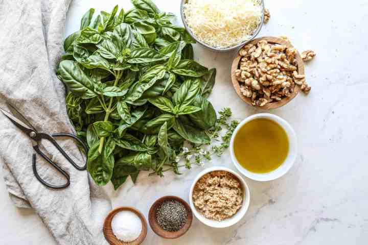 ingredients for pesto: basil, parmesan cheese, walnuts, olive oil, minced garlic, black pepper and sea salt