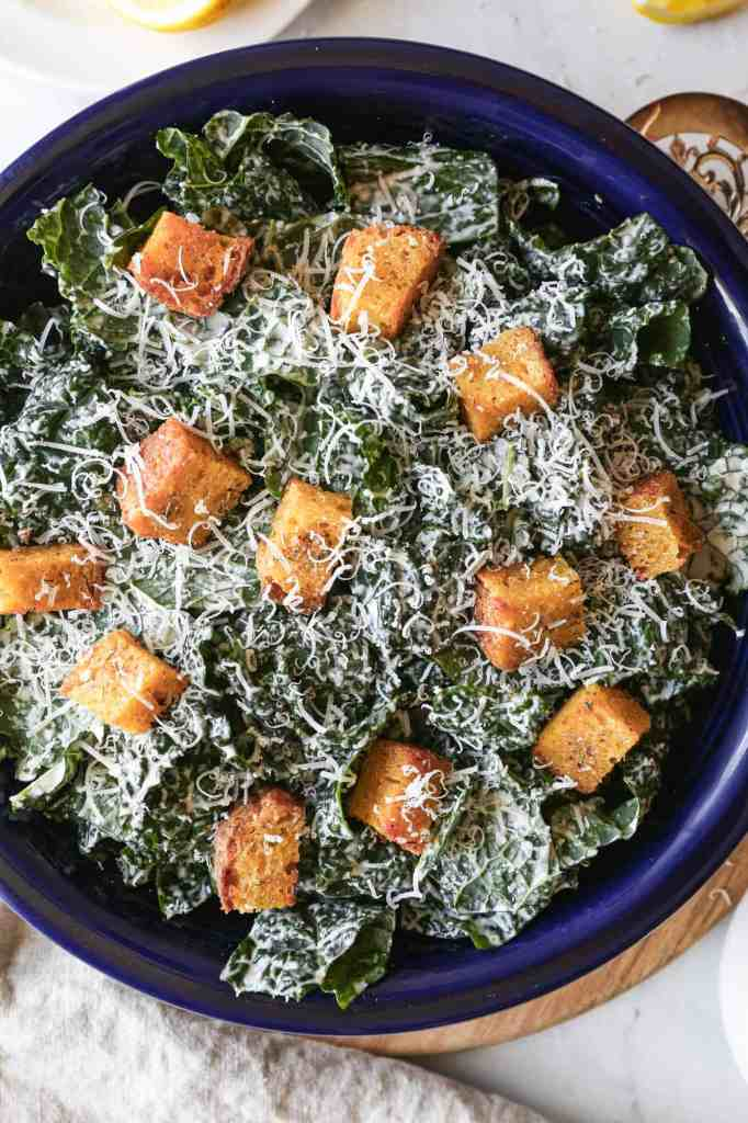 a large bowl of gluten free kale caesar salad with croutons and parmesan cheese on top