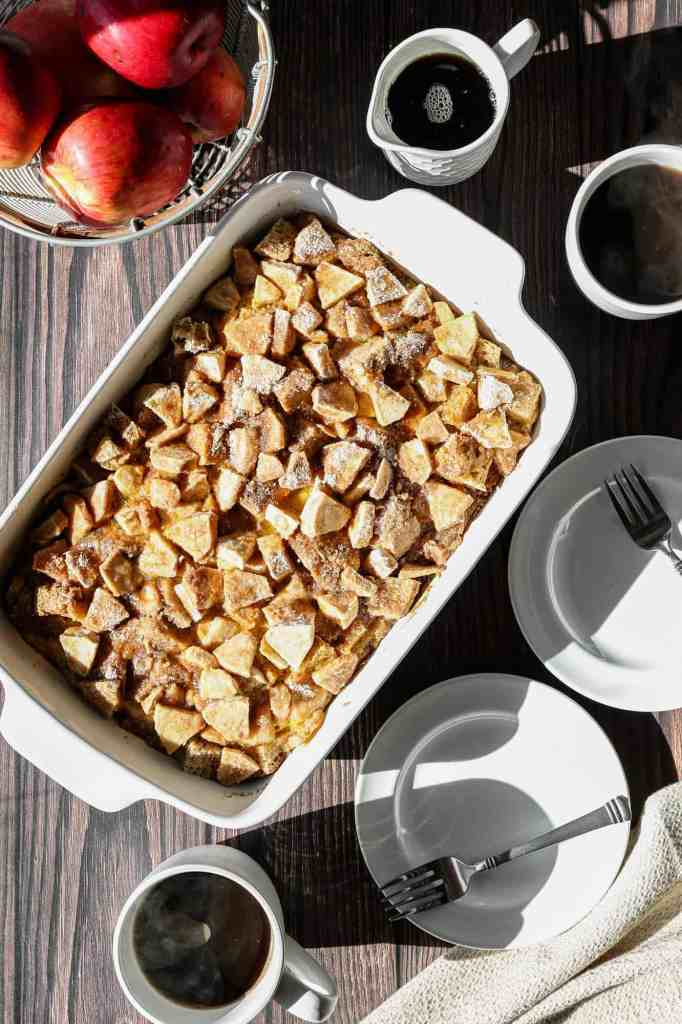 a baking dish of gluten free apple cinnamon french toast casserole with coffee and maple syrup