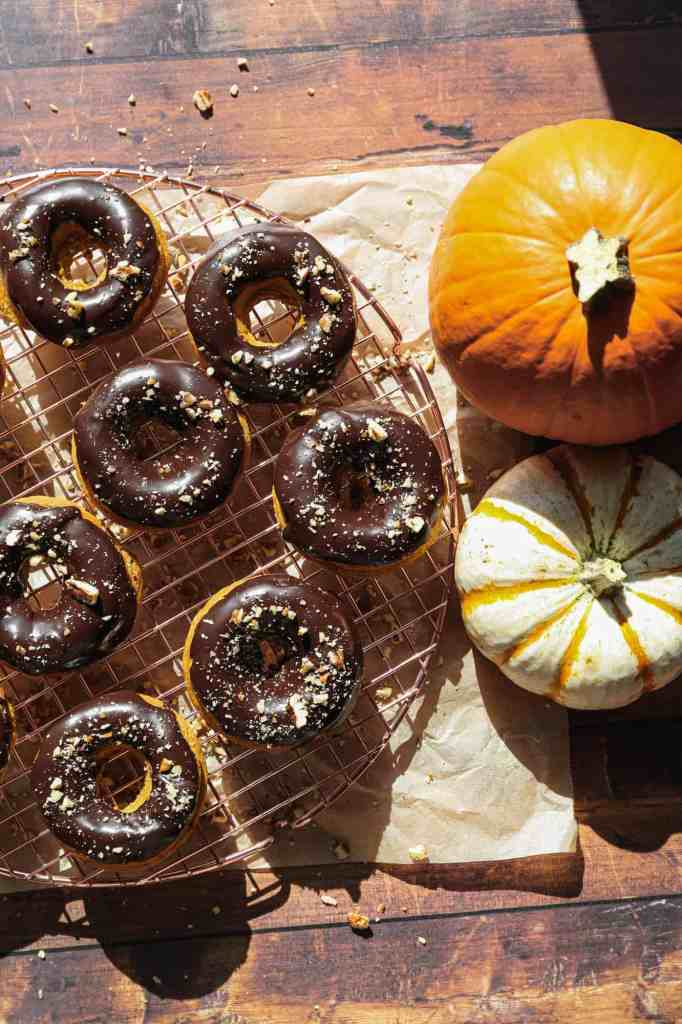 gluten free baked pumpkin donuts with chocolate glaze on a cooling rack