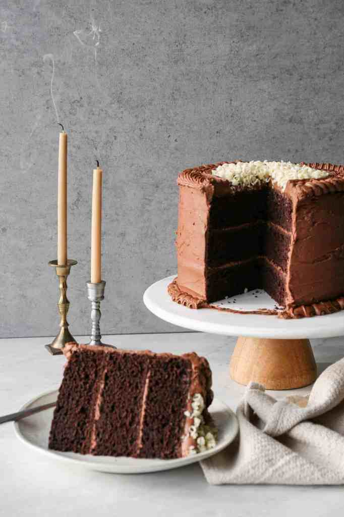 a gluten free chocolate mayonnaise cake on a cake stand with a slice of cake on a plate