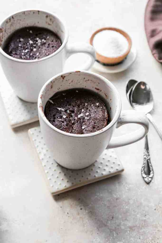 two white coffee cups of low carb gluten free chocolate mug cake with coarse sea salt sprinkled on top