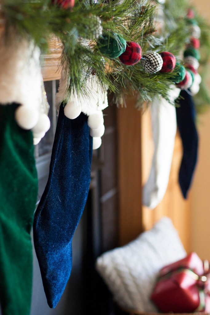 These velvet stockings with pom poms are adorable! I am in love with this Christmas mantel decor! christmas home tour | holiday homes | christmas house | christmas tree pictures | christmas mantel | christmas living room | christmas blog home tour