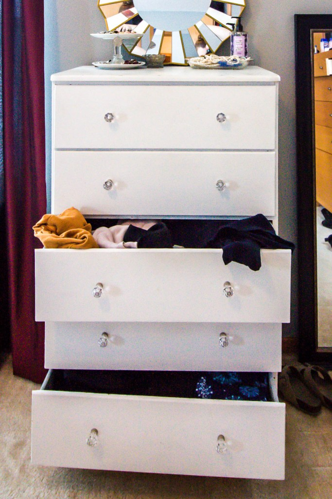 messy-sweaters-sticking-out-of-white-dresser