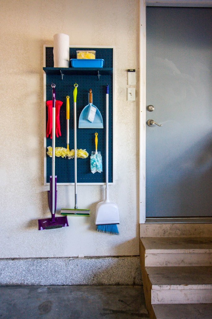 brooms-and-mops-hanging-on-pegboard-in-garage