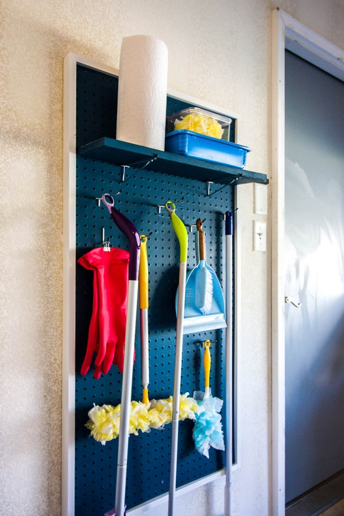 navy-pegboard-in-garage-with-brooms-on-it