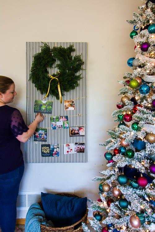 woman-hanging-christmas-card-on-wall-display