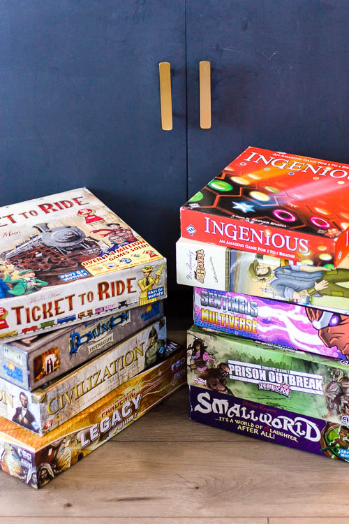 two-stacks-of-board-games-on-floor