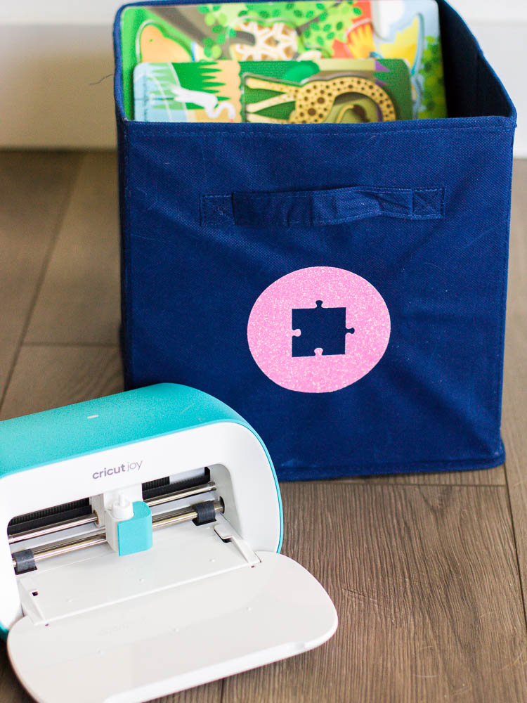 navy fabric bin with pink puzzle label and cricut joy machine