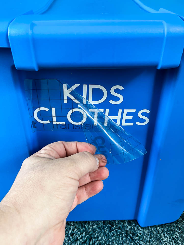 "blue plastic tote with ""kids clothes"" label in white vinyl"