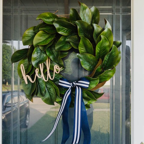 magnolia wreath with wood hello sign and striped bow