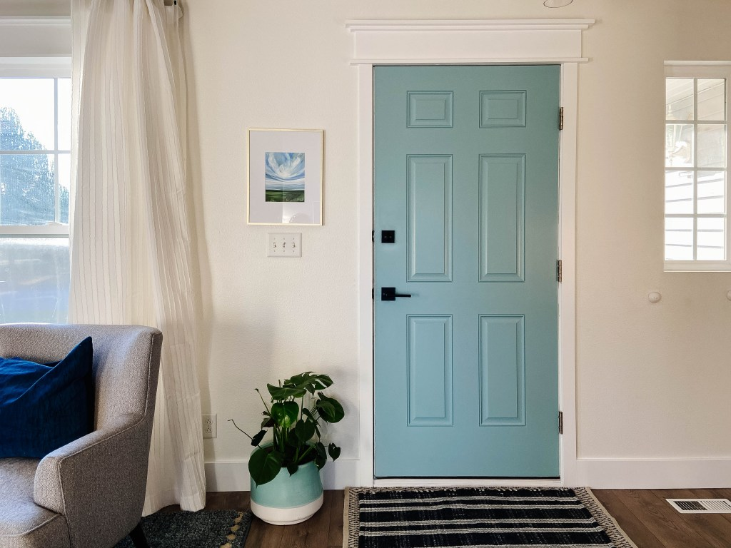 blue front door interior with dark modern hardware
