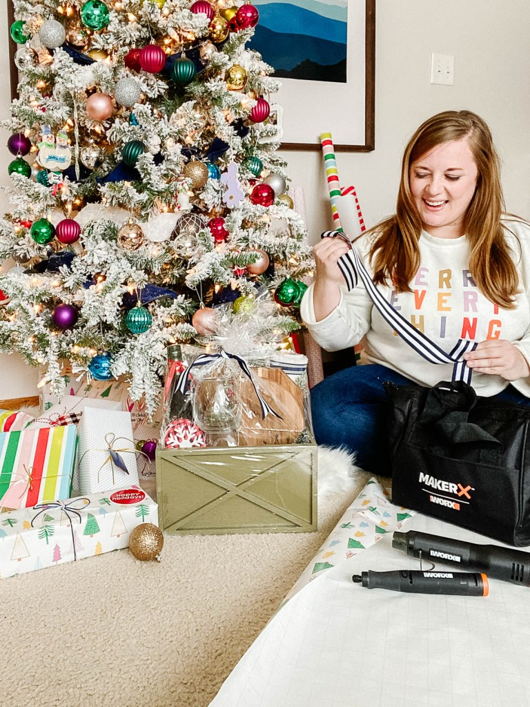 emily wrapping gifts with MakerX and gift basket by tree