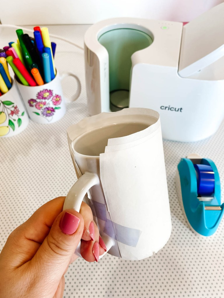 Hand holding DIY mug made with Cricut Mug Press