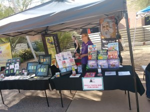 michelle buvala stands at a table full of books and art