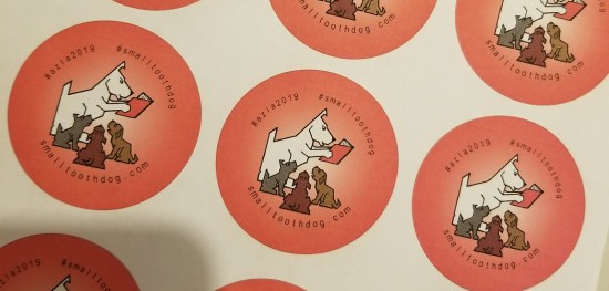 pictures of small tooth dog button showing our logo do reading a book to three puppies. drawing. hashtag azla2019 and smalltoothdog