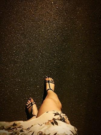 Black sandals on hot concrete