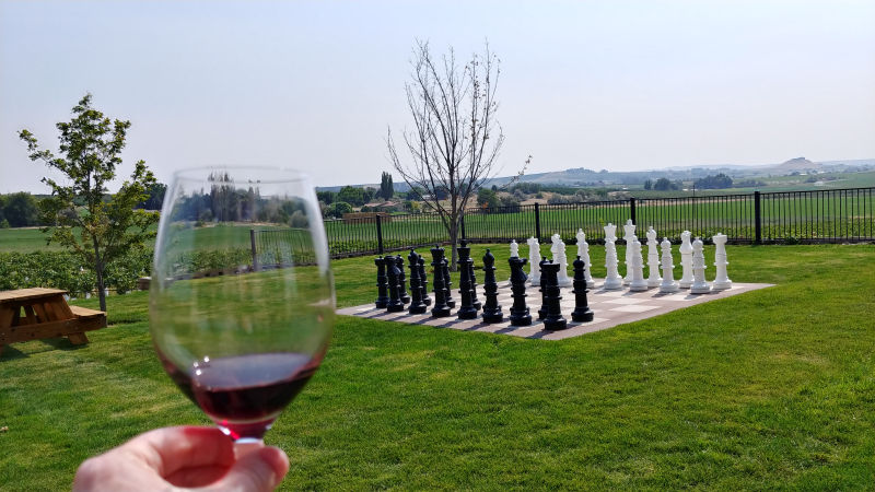 A glass of wine and a large chess set at Keonig Winery in Idaho.
