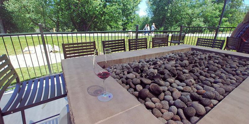 A glass of wine next to the outdoor fireplace at Telaya Wine Co. in Garden City, Idaho.