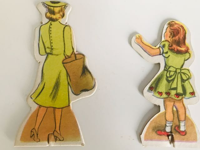 cardboard cut-outs. Back views of lady and child dressed in green dresses