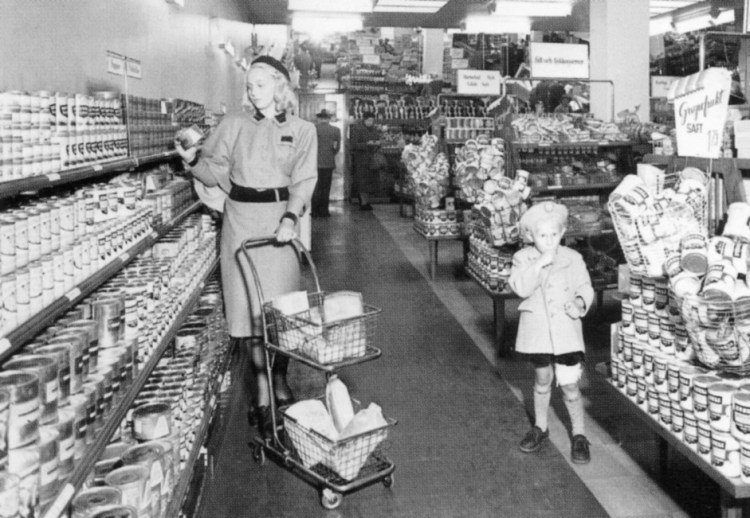Photo from 1941 showing a woman and a boy in an aisle in a super market.