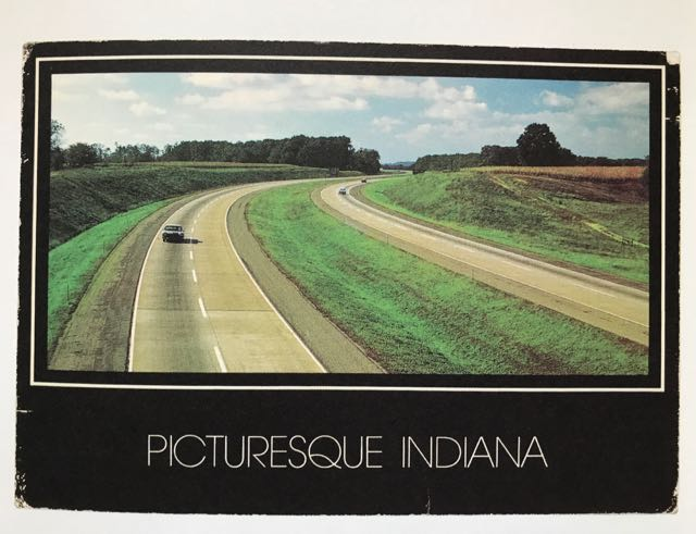 photo of a page from Martin Parr's 'Boring Postcards - USA'. In colour. Text: Picturesque Indiana. showing single car on otherwise deserted motorway