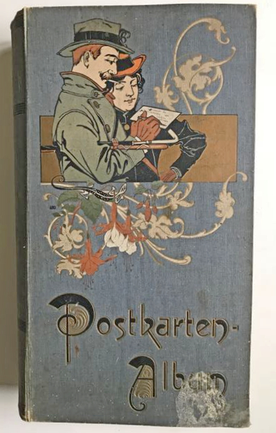 cover of postcard album from around 1910 showing man and woman. The man is writing a card while the woman watches on.
