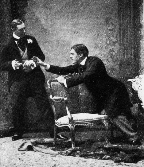 still photo from Act 1 of the original production of the play (1895) shows Algernon Moncrieff (left, played by Allan Aynesworth) refusing to return Mr Jack Worthing's (Sir George Alexander) cigarette case