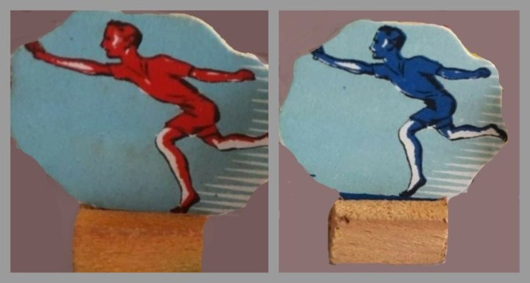 photo of 2 player figurines made from cardboard. one red on light blue background, one dark blue on light blue background. Cardboard disc is stuck in wooden implement.
