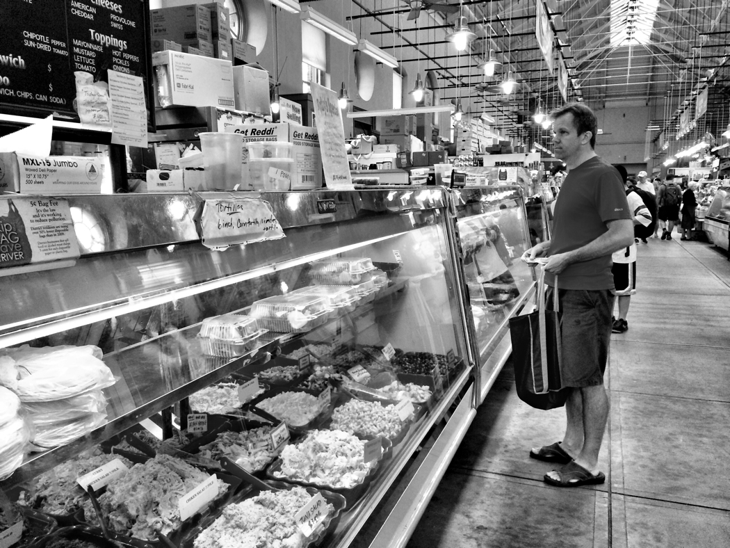 A man with a shopping list waits to be served at a stall in Eastern market in Washington DC