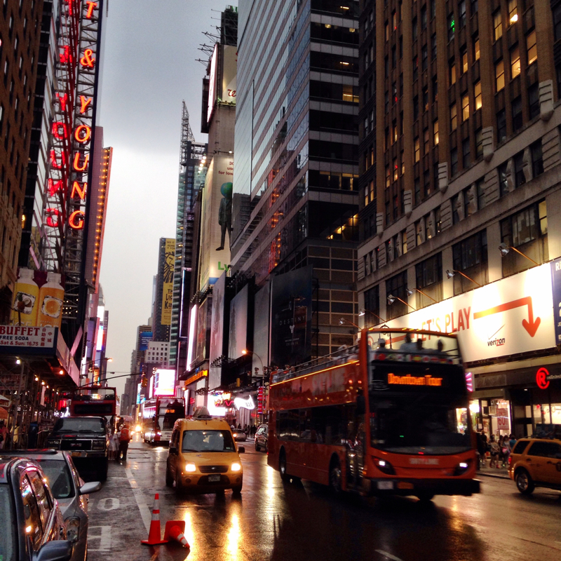 A tourist bus drives down a New York street as the rain starts to fall