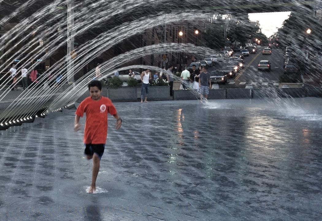 Kid in orange shirt running in the water fountain in Georgetown, Washington DC