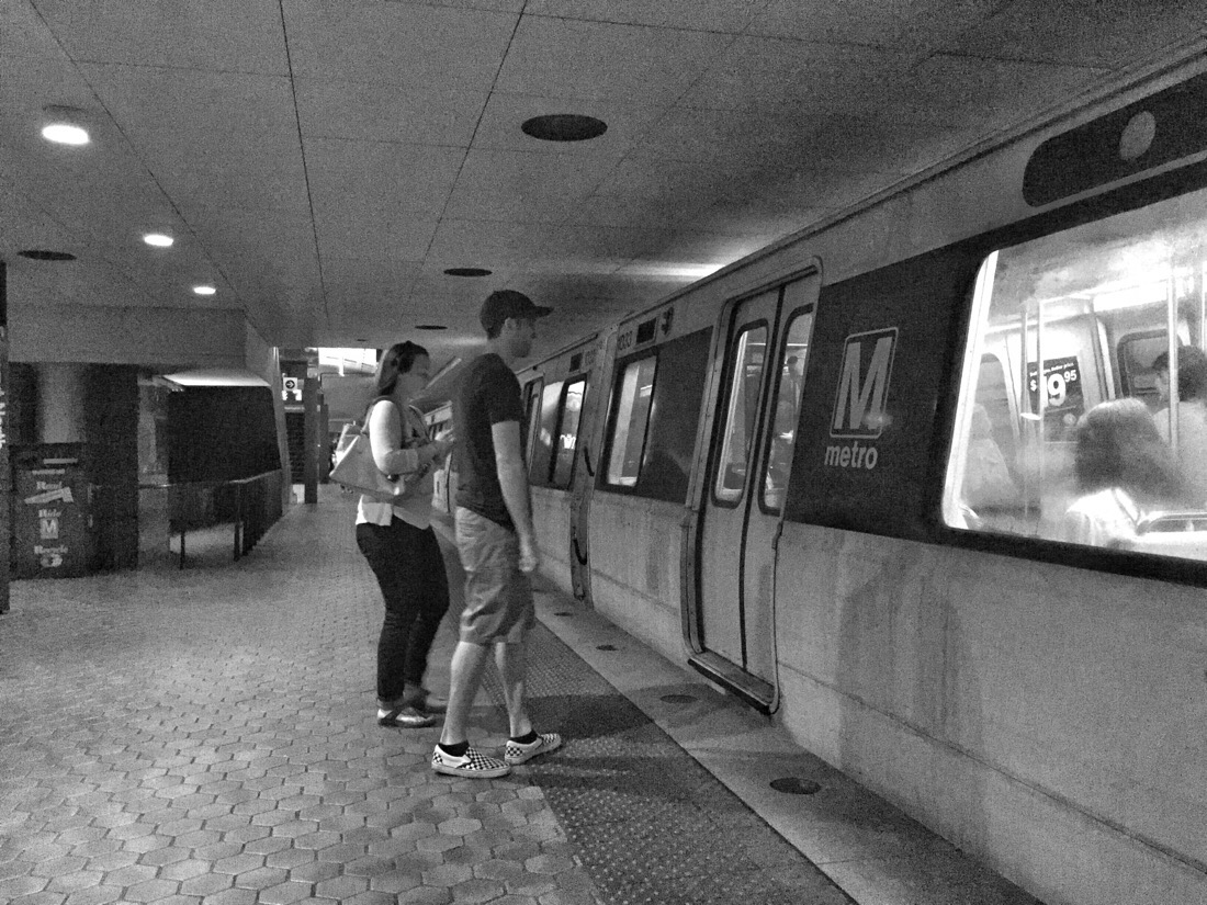 two people boarding a Metro train at Farragut North Metro Station in Washington DC