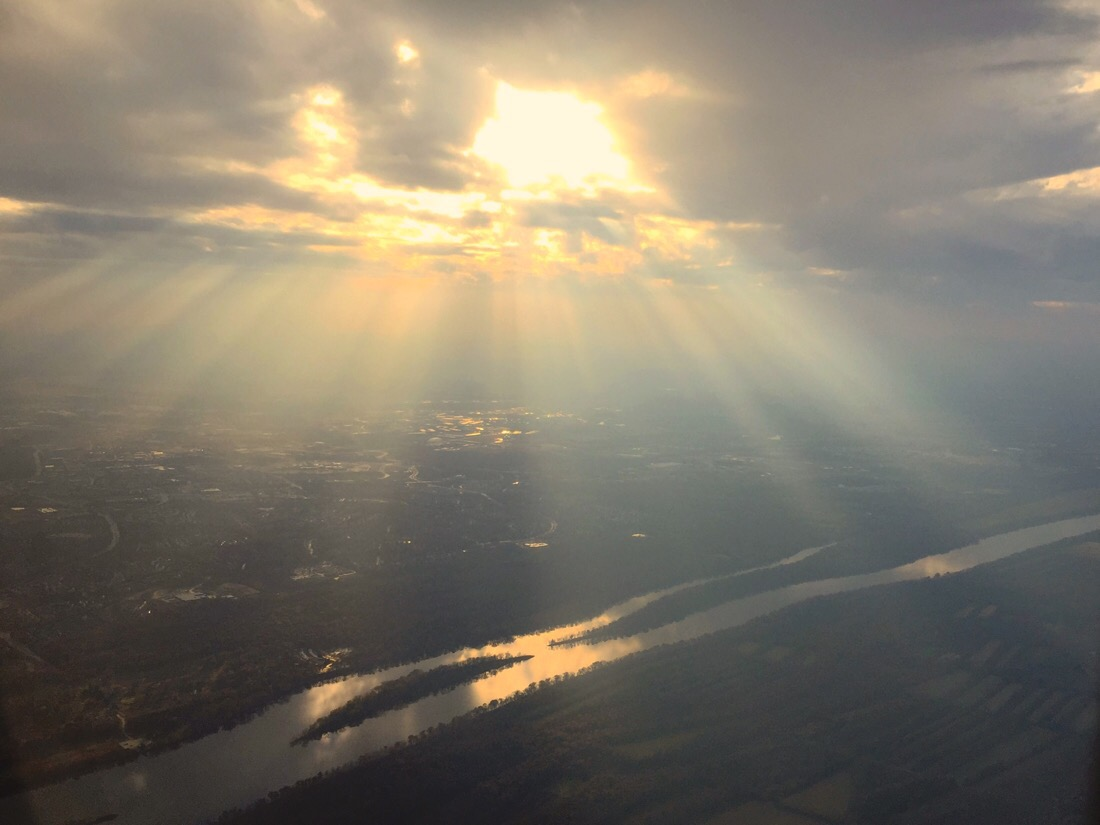 The sun sets and streams through the clouds as the plane approaches Dulles airport