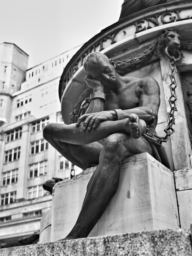 One of the manacled figures on the base of the Nelson monument on exchanges flags in Liverpool, England.