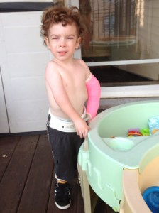 Playing at the water table with no water since we can't get his cast wet.  Funny how he still loves playing here.
