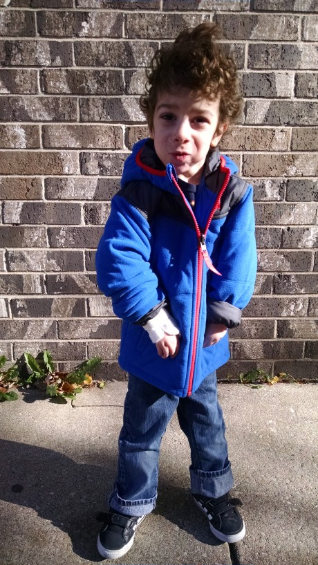 Aleck modeling his new coat outside of his preschool.