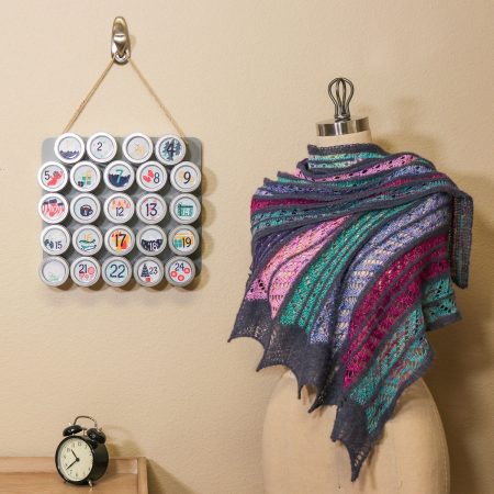 A multi colored shawl is on a dress form with the craftvent calendar hanging on the wall behind it