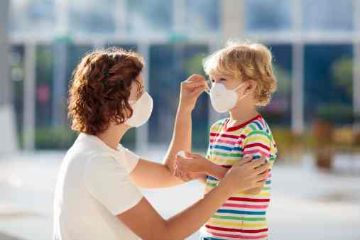 woman helping a preschooler with a face mask